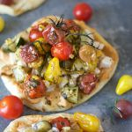 Mini naan topped with hummus, chicken and roasted tomatoes, zucchini and corn tossed in pesto.