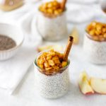 Apple Pie Chia Pudding in small jars topped with cooked apples and a cinnamon stick.