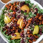 Autumn-Harvest Salad with roasted sweet potato, apple, cherries and wild rice in a large serving bowl.