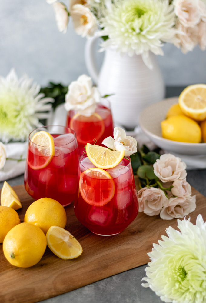 Iced Passion Tea Lemonade in glasses sitting on a cutting board with fresh flowers