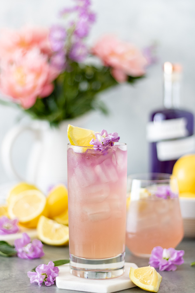 Two glasses of Empress Gin Lemonade surrounded by fresh lemons, flowers and a bottle of Empress 1908 Gin
