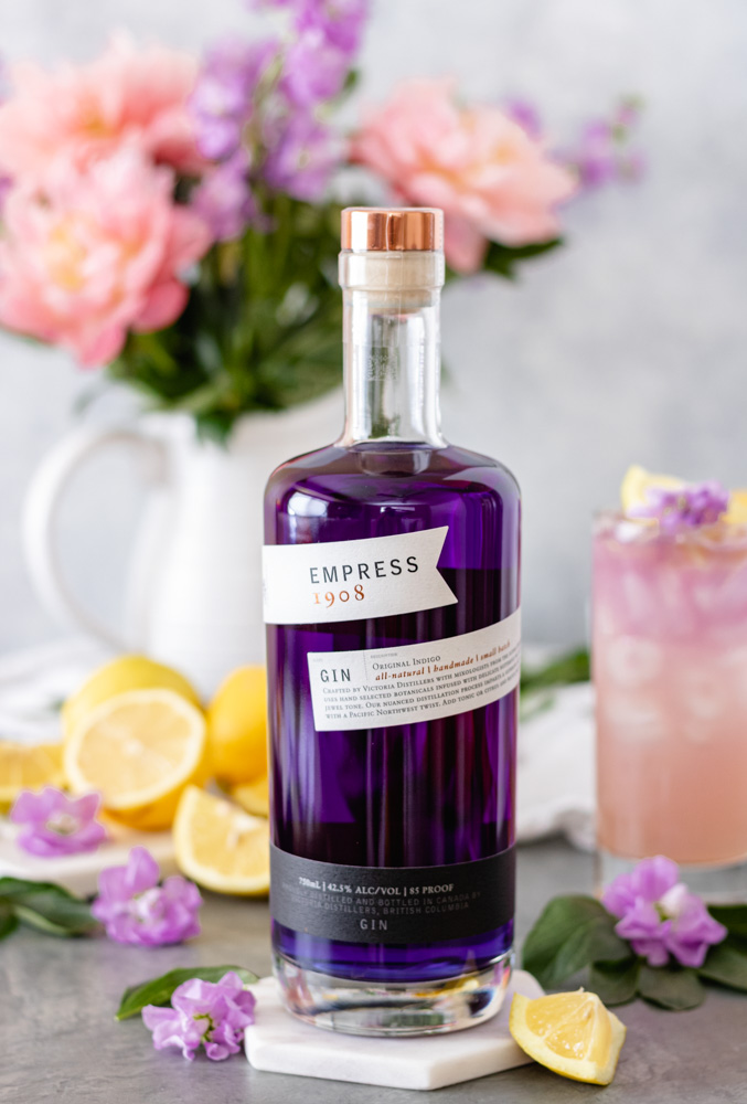 A bottle of Empress 1908 Gin surrounded by a glass of Empress Gin Lemonade, fresh lemons and flowers