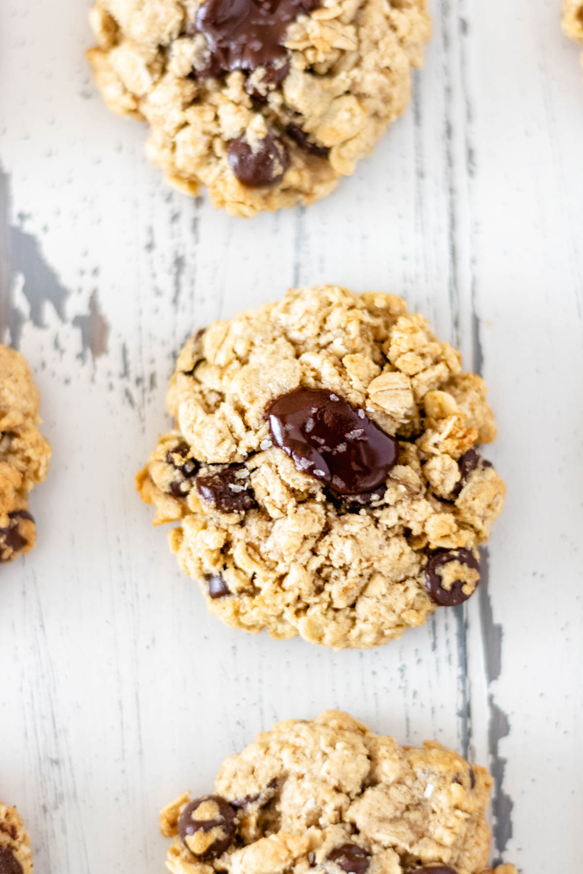 Three soft and chewy Dark-Chocolate Chip Oatmeal Cookies in a row.