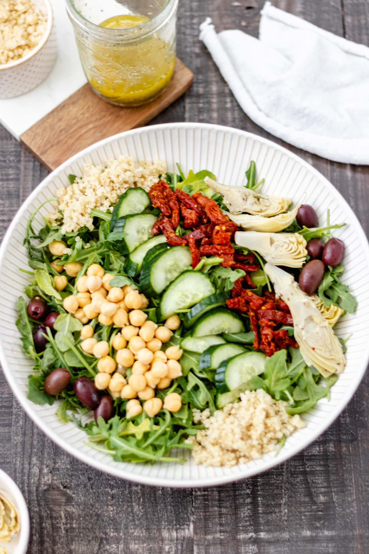 Mediterranean salad ingredients, like artichoke hearts, Kalamata olives, sundried tomatoes and arugula in a large serving bowl that is surrounded by other ingredients in glass jars.
