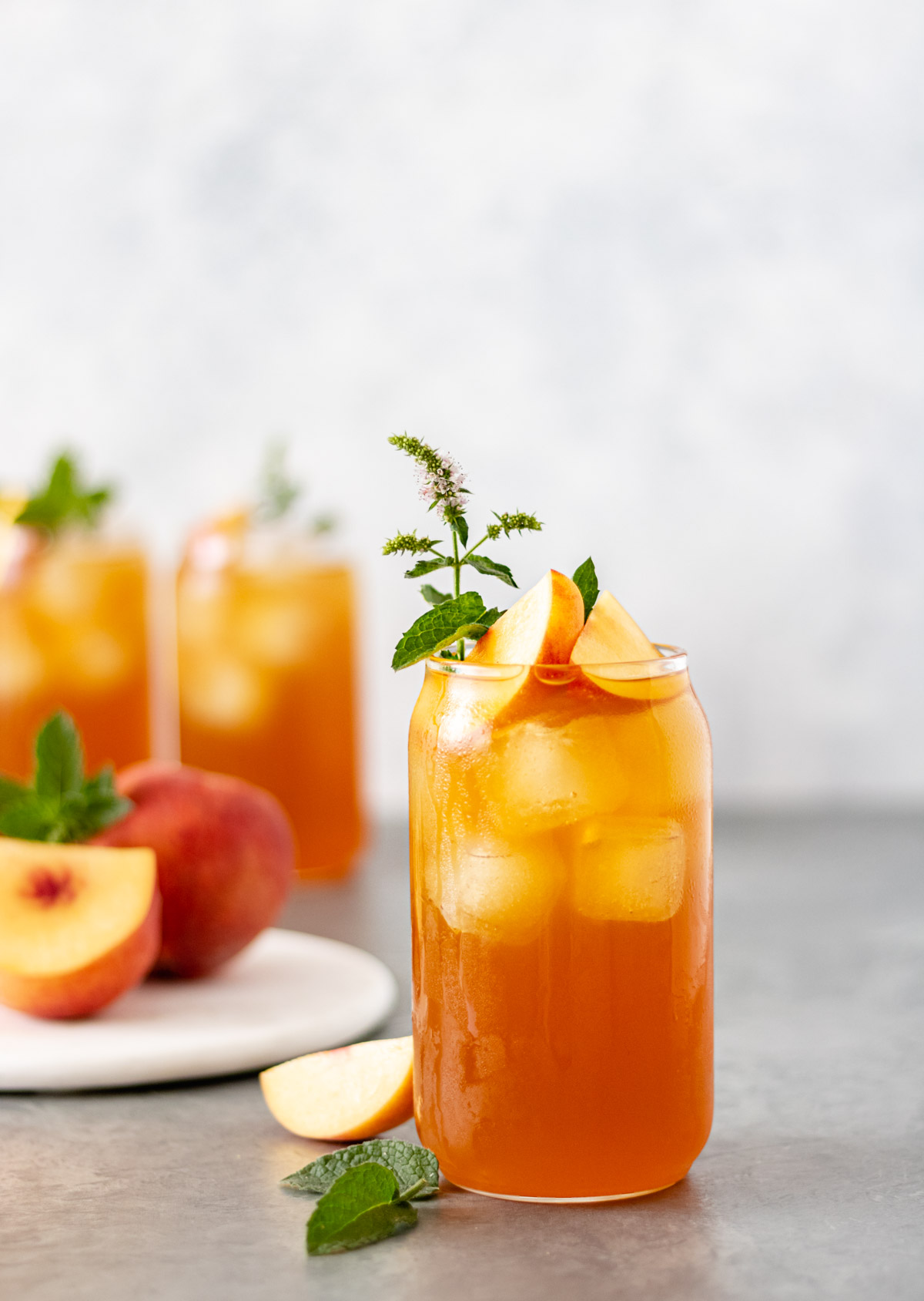 A glass filled with peach lavender iced tea, fresh peach slices and mint.