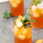 Three glasses filled with peach lavender iced tea, fresh peach slices and mint.