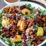 Autumn-Harvest Salad with roasted sweet potato, apple, cherries and wild rice in a large serving bowl and dressing on the side.